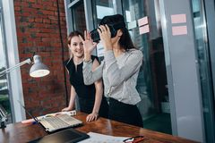 Δύο γυναίκες σπουδαστές που παίζουν ένα τρισδιάστατο παιχνίδι στα γυαλιά VR που έχουν ένα κενό μετά από ένα μάθημα στην τάξη στοκ εικόνες