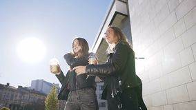 Δύο γυναίκες σπουδαστές που περπατούν κάτω από την οδό κατά τη διάρκεια του σπασίματος και που μιλούν χαρωπά την ηλιόλουστη ημέρα απόθεμα βίντεο