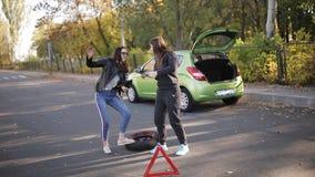 Δύο γυναίκες στην άκρη του δρόμου που χορεύει κοντά στο αυτοκίνητο με μια σπασμένη ρόδα, που προσελκύει την προσοχή των οδηγών απόθεμα βίντεο
