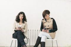 Δύο γυναίκες στη αίθουσα αναμονής που φαίνονται smartphone σοβαρό στοκ εικόνες με δικαίωμα ελεύθερης χρήσης