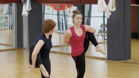 Δύο γυναίκες στη γυμναστική κάνουν τις σύνθετες γυμναστικές ασκήσεις στεμένος σε ένα πόδι απόθεμα βίντεο