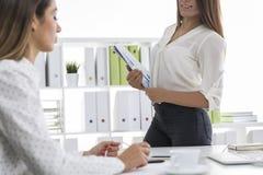 Δύο γυναίκες στις άσπρες μπλούζες εργάζονται σε ένα γραφείο Στοκ εικόνα με δικαίωμα ελεύθερης χρήσης