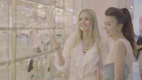 Δύο γυναίκες στις αγορές επιλέγουν κάτι στο κατάστημα φιλμ μικρού μήκους