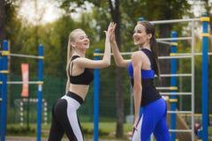 Δύο γυναίκες στις φόρμες γυμναστικής γιορτάζουν τη νίκη Στοκ φωτογραφία με δικαίωμα ελεύθερης χρήσης