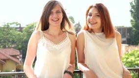 Δύο γυναίκες στο γέλιο των μπαλκονιών και το χαμόγελο ενώ βρέχει εξωτερικός και τον αέρα αυτό φυσούν μέσω εκεί της τρίχας απόθεμα βίντεο