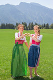 Δύο γυναίκες στο dirndl που διαμορφώνει μια καρδιά με τα χέρια της Στοκ Φωτογραφία