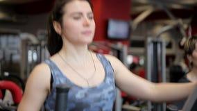 Δύο γυναίκες συμμετέχουν στις μηχανές άσκησης στη γυμναστική Trenerovka των γυναικών Τα κορίτσια κάνουν τις ασκήσεις σε ένα παράθ απόθεμα βίντεο