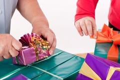 Δύο γυναίκες τυλίγουν ή ανοίγουν τα δώρα Στοκ εικόνα με δικαίωμα ελεύθερης χρήσης