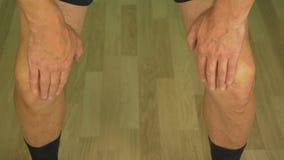 Δύο γόνατα του ενήλικου καυκάσιου ατόμου Αρσενικό που τρίβει τα πόδια του με το χέρι την παλάμη απόθεμα βίντεο