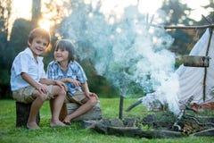 Δύο γλυκά παιδιά, αδελφοί αγοριών, που στρατοπεδεύουν έξω από το καλοκαίρι επάνω στοκ φωτογραφίες
