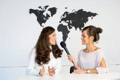 Δύο δίδυμα δημοσιογράφων κοριτσιών υποβάλλουν έκθεση από ένα άσπρο στούντιο Στοκ εικόνα με δικαίωμα ελεύθερης χρήσης