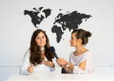 Δύο δίδυμα δημοσιογράφων κοριτσιών υποβάλλουν έκθεση από ένα άσπρο στούντιο Στοκ Εικόνα