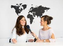 Δύο δίδυμα δημοσιογράφων κοριτσιών υποβάλλουν έκθεση από ένα άσπρο στούντιο Στοκ Εικόνες