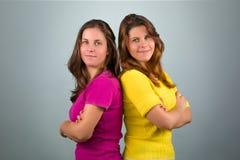Δύο δίδυμες αδελφές με τα διασχισμένα όπλα στοκ φωτογραφίες