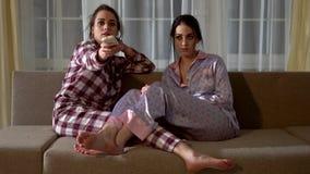 Δύο δίδυμες αδελφές στις πυτζάμες κάθονται στον καναπέ και επιλέγουν τι να προσέξει στη TV στο καθιστικό σχέση απόθεμα βίντεο