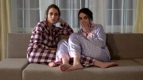 Δύο δίδυμες αδελφές στις πυτζάμες κάθονται στον καναπέ και επιλέγουν τι να προσέξει στη TV στο καθιστικό σχέση φιλμ μικρού μήκους