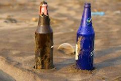 Δύο διαφορετικά μπουκάλια γυαλιού χρώματος στην παραλία σε Palande στοκ φωτογραφία