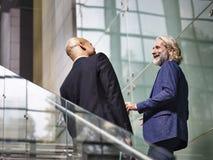 Δύο διοικητικοί συνεργάτες που μιλούν ανερχόμενος τα σκαλοπάτια Στοκ εικόνα με δικαίωμα ελεύθερης χρήσης