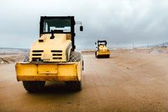 Δύο δονητικοί εδαφολογικοί συμπιεστές στο εργοτάξιο οικοδομής Βιομηχανικά οδικά έργα στην εθνική οδό με τα βαρέων καθηκόντων μηχα στοκ φωτογραφία με δικαίωμα ελεύθερης χρήσης