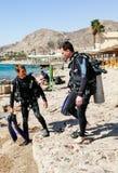 Δύο δύτες σκαφάνδρων στα κοστούμια για την κατάδυση σκαφάνδρων πηγαίνουν στο νερό κοντά στην πόλη Eilat στο Ισραήλ Στοκ φωτογραφία με δικαίωμα ελεύθερης χρήσης