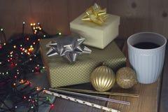 Δύο δώρα, σφαίρες και γλυκά ραβδιά ν φλιτζανιών του καφέ Χριστουγέννων Στοκ Εικόνες