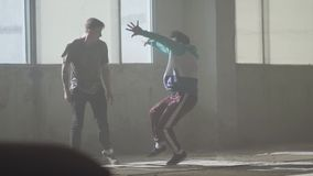 Δύο ειδικευμένοι χορευτές που χορεύουν μπροστά από το μεγάλο παράθυρο στο εγκαταλειμμένο κτήριο Έφηβοι που κάνουν την κίνηση χορο φιλμ μικρού μήκους