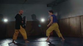 Δύο ελεύθεροι μαχητές που εκπαιδεύουν τα λακτίσματα και τις υποδοχές στη γυμναστική αργά φιλμ μικρού μήκους