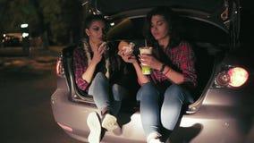 Δύο ελκυστικές φίλες που κάθονται στον ανοικτό κορμό του αυτοκινήτου, που μιλούν και που τρώνε τα σάντουιτς, που πίνουν από το έγ φιλμ μικρού μήκους