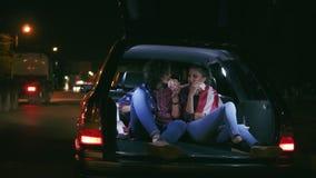 Δύο ελκυστικές φίλες που κάθονται στον ανοικτό κορμό του αυτοκινήτου, που μιλούν και που τρώνε τα burgers κατά τη διάρκεια της νύ φιλμ μικρού μήκους