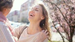 Δύο ενήλικες γυναίκες που αγκαλιάζουν και που γελούν Υπαίθριο πορτρέτο άνοιξη απόθεμα βίντεο