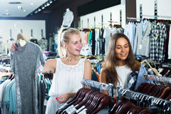 Δύο ενήλικα χαμογελώντας κορίτσια που επιλέγουν το φόρεμα από κοινού στοκ φωτογραφία με δικαίωμα ελεύθερης χρήσης