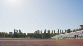 Δύο ενεργοί δρομείς που ανταγωνίζονται στο στάδιο, που εκπαιδεύει σκληρά να επιτύχει την αθλητική επιτυχία απόθεμα βίντεο