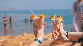Δύο εξωτικά κοκτέιλ στα χέρια των κοριτσιών στο υπόβαθρο της θάλασσας και της παραλίας στην Αίγυπτο φιλμ μικρού μήκους