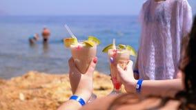 Δύο εξωτικά κοκτέιλ στα χέρια των κοριτσιών στο υπόβαθρο της θάλασσας και της παραλίας στην Αίγυπτο απόθεμα βίντεο