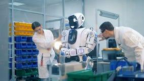 Δύο επαγγελματίες επιθεωρούν ένα ρομποτικό humanoid απόθεμα βίντεο