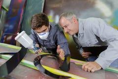 Δύο επαγγελματικοί εργαζόμενοι ζωγράφων εργοστασίων που χρωματίζουν το μέταλλο Στοκ εικόνες με δικαίωμα ελεύθερης χρήσης