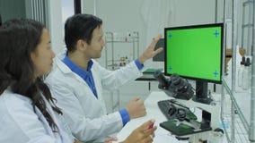 Δύο επιστήμονες ιατρικής έρευνας που εξετάζουν την πράσινη οθόνη στο σύγχρονο εργαστήριο απόθεμα βίντεο