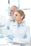Δύο επιστήμονες στα άσπρα παλτά και προστατευτικά δίοπτρα που κοιτάζουν μακριά και που θέτουν Στοκ Εικόνες