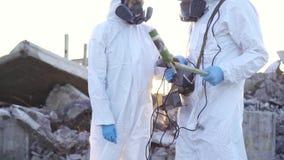 Δύο επιστήμονες στα προστατευτικές κοστούμια και τις μάσκες και κάνουν τις μετρήσεις του προσωπικού δοσιμέτρου ακτινοβολίας ιονισ φιλμ μικρού μήκους