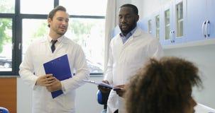 Δύο επιστήμονες τινάζουν τα χέρια περπατώντας στο σύγχρονο εργαστήριο εξετάζοντας τα θηλυκά reseachers κάνοντας την ανάλυση πειρά απόθεμα βίντεο