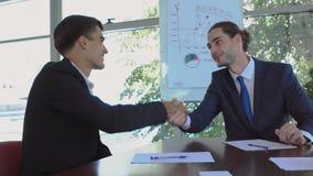 Δύο επιχειρηματίες κάνουν μια διαπραγμάτευση στο γραφείο απόθεμα βίντεο