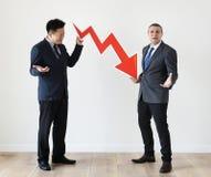 Δύο επιχειρηματίες με το οικονομικό λογότυπο εικονιδίων ποσοστού μείωσης Στοκ Φωτογραφίες