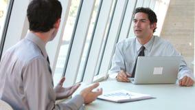 Δύο επιχειρηματίες με το lap-top που διοργανώνει τη συνεδρίαση φιλμ μικρού μήκους