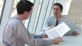 Δύο επιχειρηματίες με το lap-top που διοργανώνει τη συνεδρίαση απόθεμα βίντεο