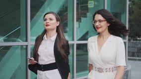 Δύο επιχειρηματίες μιλούν πηγαίνουν οι νέες ελκυστικές γυναίκες περπατούν κάτω από την οδό φιλμ μικρού μήκους