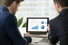 Δύο επιχειρηματίες που αναλύουν τις στατιστικές προγράμματος όσον αφορά την οθόνη lap-top Στοκ φωτογραφία με δικαίωμα ελεύθερης χρήσης