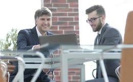 Δύο επιχειρηματίες που εργάζονται μαζί χρησιμοποιώντας το lap-top στην επιχειρησιακή συνεδρίαση στην αρχή Στοκ Εικόνα
