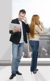 Δύο επιχειρηματίες που εργάζονται με ένα lap-top και ένα τηλέφωνο Στοκ Εικόνα