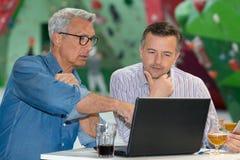 Δύο επιχειρηματίες που εργάζονται στο φραγμό Στοκ Εικόνες