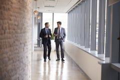 Δύο επιχειρηματίες που διοργανώνουν την άτυπη συνεδρίαση στο διάδρομο γραφείων Στοκ Εικόνες